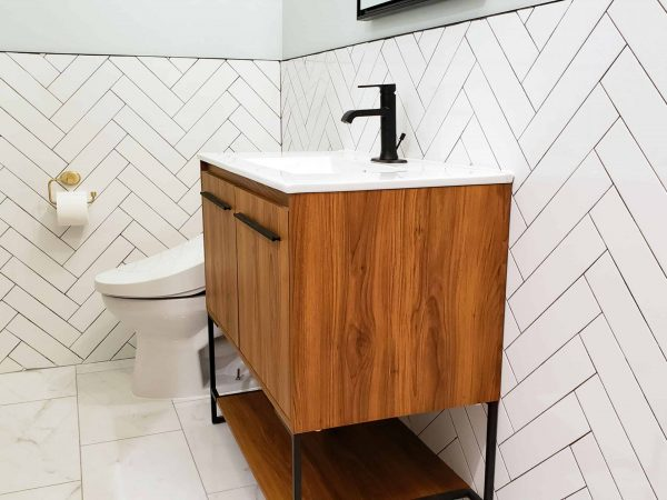 modern bathroom with large format porcelain tile floor, herringbone walls, and updated sink